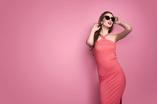Portret van jonge mooie slanke sexy jonge vrouw in sexy kleding met rode sensuele binnen lippen op roze muur