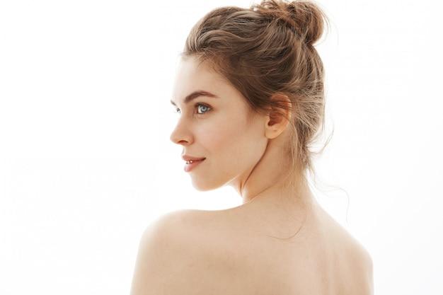 Portret van jonge mooie tedere naakte vrouw met broodje dat zich over witte achtergrond bevindt.