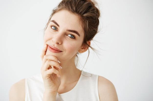 Portret van jonge mooie tedere vrouw met broodje glimlachend aanraken gezicht