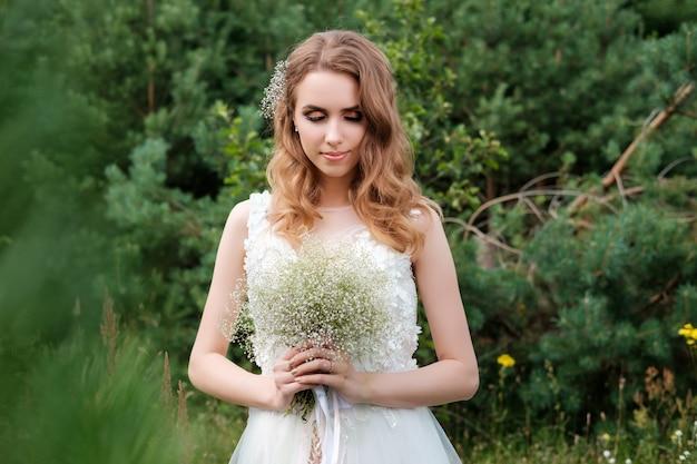 Portret van jonge mooie vrouw (bruid) in witte huwelijkskleding in openlucht, kapsel
