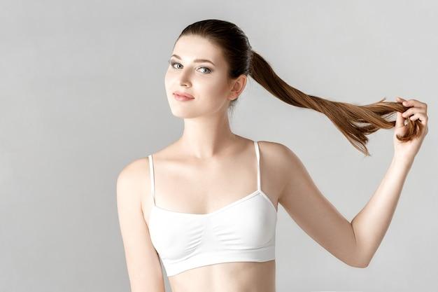 Portret van jonge mooie vrouw brunette met met lang haar natuurlijke make-up in witte lingerie