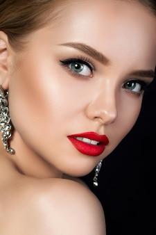 Portret van jonge mooie vrouw close-up met avond make-up kijkt over haar schouder. rode lippen en eyeliner. klassiek make-upconcept.