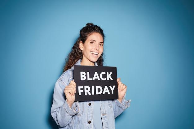 Portret van jonge mooie vrouw die black friday-aanplakbiljet houdt en tegen de blauwe achtergrond glimlacht