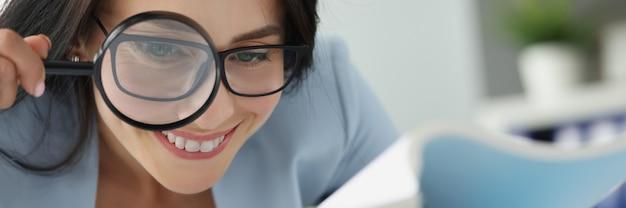 Portret van jonge mooie vrouw die documenten door vergrootglas onderzoekt