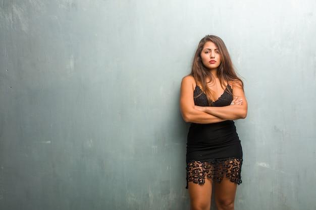Portret van jonge mooie vrouw die een kleding draagt tegen een muur zeer boos en verstoord, zeer gespannen, schreeuwend woedend, negatief en gek