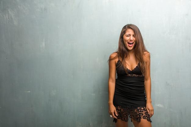 Portret van jonge mooie vrouw die een kleding draagt tegen een muur zeer boos en verstoord