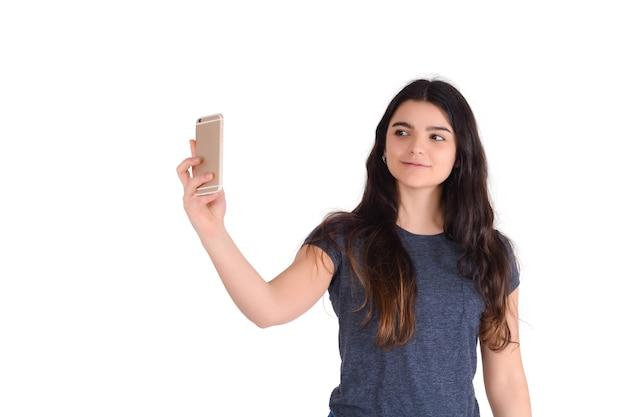 Portret van jonge mooie vrouw die een selfie met haar mobiele telefoon neemt die in een studio wordt geïsoleerd