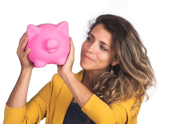 Portret van jonge mooie vrouw die een spaarvarken op studio houdt. geïsoleerde witte achtergrond. bespaar geld concept.