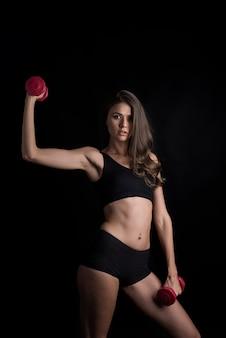 Portret van jonge mooie vrouw die fysieke oefeningen met domoren maken
