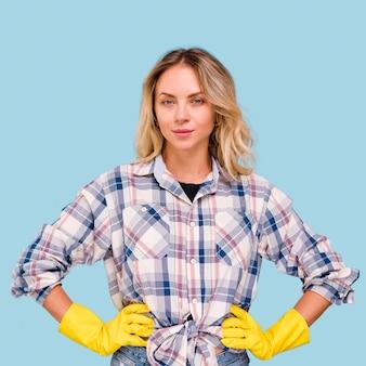 Portret van jonge mooie vrouw die gele handschoenen draagt die camera bekijken
