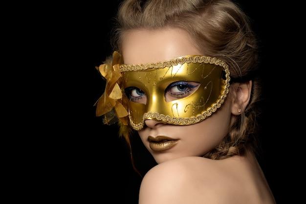 Portret van jonge mooie vrouw die gouden partijmasker draagt. carnaval van venetië, gemaskerd bal of nieuwjaarsfeest.