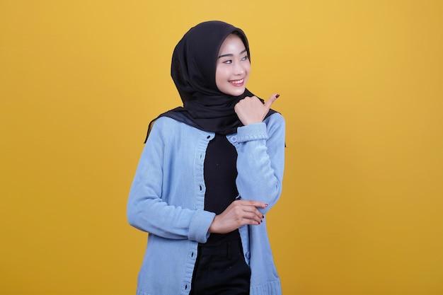 Portret van jonge mooie vrouw die hijab draagt, vreugdevol glimlacht en er gelukkig uitziet, zich zorgeloos en positief voelt met beide duimen omhoog