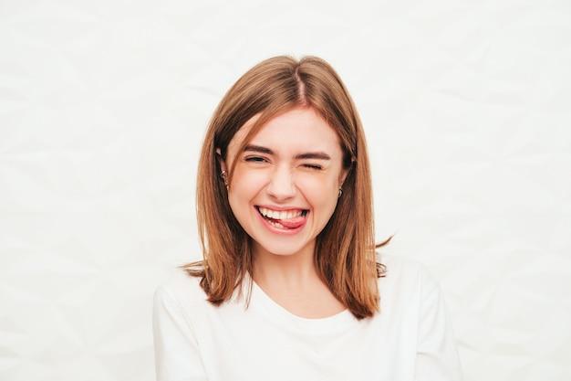 Portret van jonge mooie vrouw die naar de camera kijkt. trendy vrouw die lacht in casual zomerse hipsterkleren