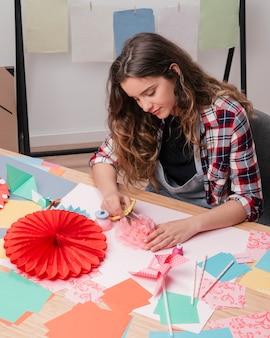 Portret van jonge mooie vrouw die origamidocument bloem maakt