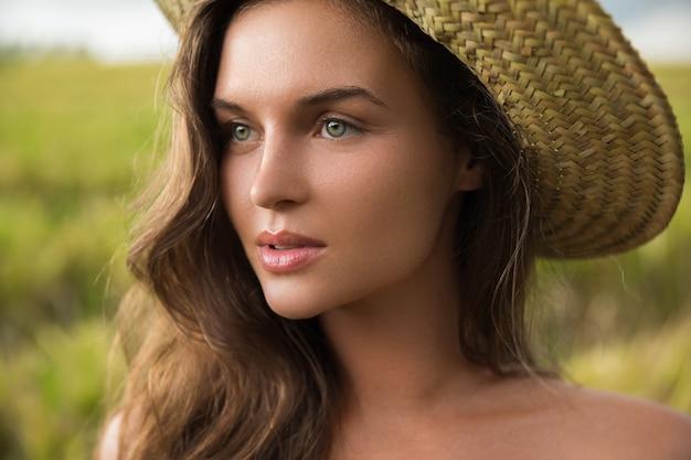 Portret van jonge mooie vrouw die strohoed draagt