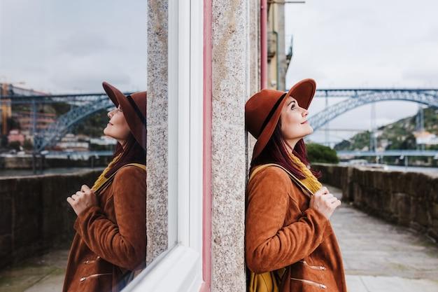 Portret van jonge mooie vrouw die zich bij porto-muur bevindt die moderne hoed draagt die van uitzicht geniet. reis concept