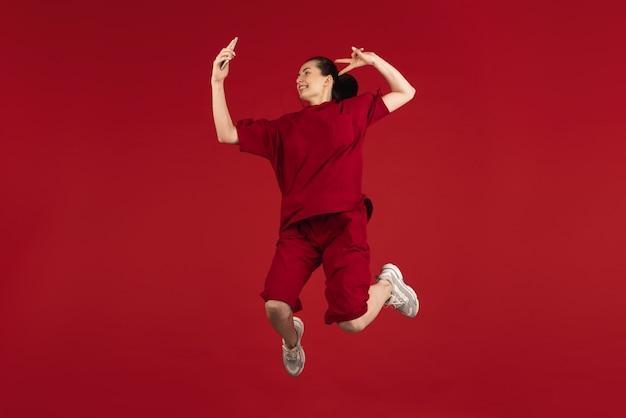 Portret van jonge mooie vrouw geïsoleerd op rode kleur studio achtergrond. concept van emoties