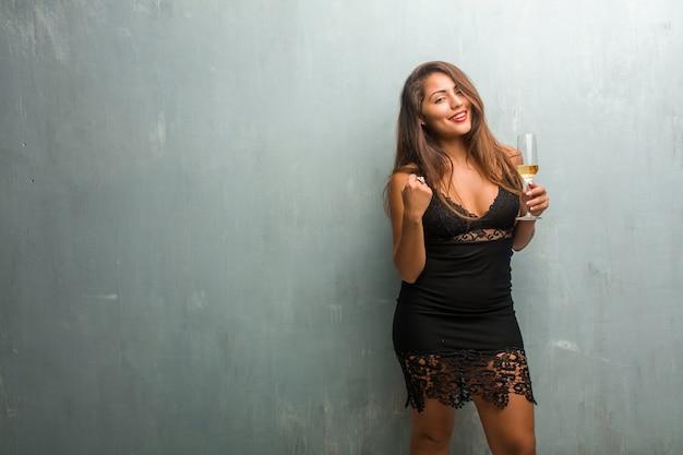 Portret van jonge mooie vrouw, gekleed in een jurk tegen een muur erg blij en opgewonden
