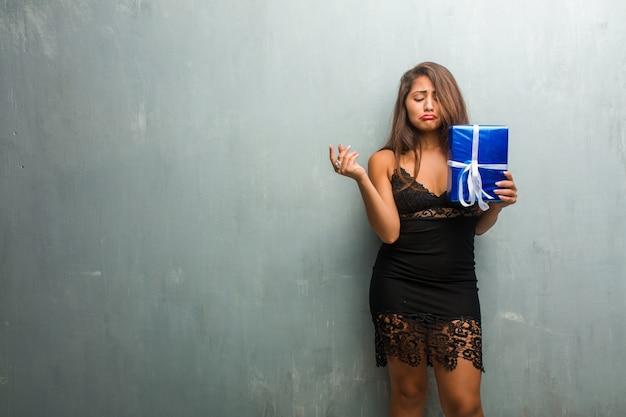 Portret van jonge mooie vrouw, gekleed in een jurk tegen een muur verdrietig en depressief