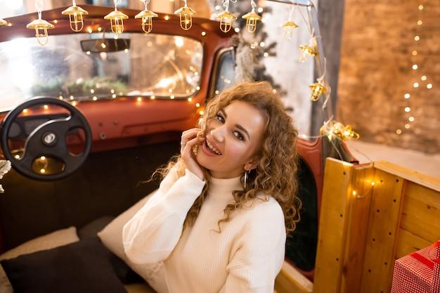 Portret van jonge mooie vrouw in auto zitten en wachten op kerstmis