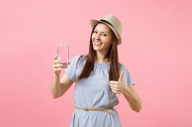Portret van jonge mooie vrouw in blauwe jurk, hoed vasthouden en drinken van helder vers zuiver water uit glas geïsoleerd op roze achtergrond. gezonde levensstijl, mensen, oprechte emoties concept. ruimte kopiëren