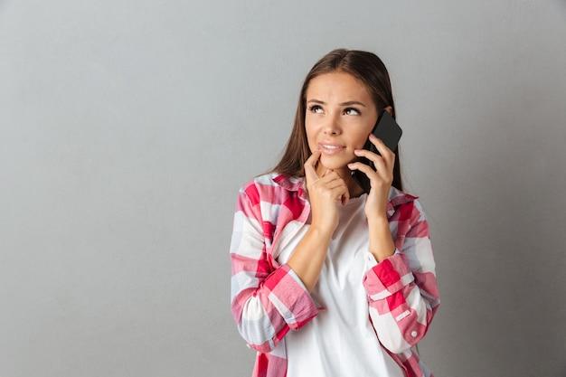 Portret van jonge mooie vrouw in geruit hemd, praten op een mobiele telefoon, wegkijken