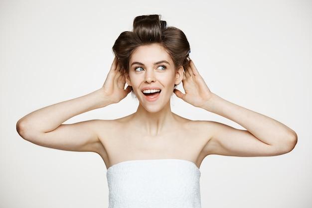 Portret van jonge mooie vrouw in haarkrulspelden en handdoek het glimlachen het stellen. cosmetologie en spa.