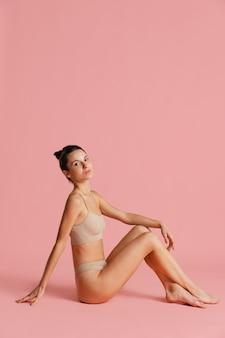 Portret van jonge mooie vrouw in lingerie poseren geïsoleerd op roze