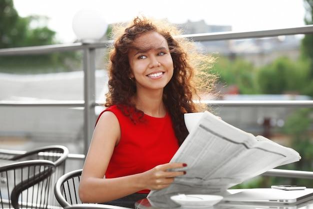 Portret van jonge mooie vrouw in rode jurk krant lezen op zomerterras at
