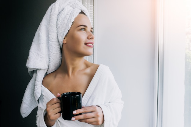 Portret van jonge mooie vrouw in witte handdoek en robe koffie drinken en genieten van in de buurt van het raam thuis