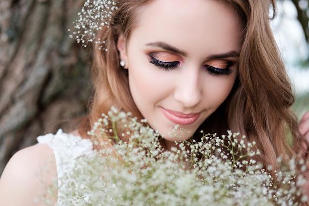 Portret van jonge mooie vrouw in witte huwelijkskleding in openlucht