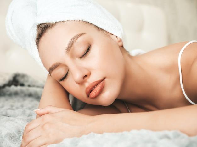 Portret van jonge mooie vrouw in witte lingerie en handdoek op hoofd