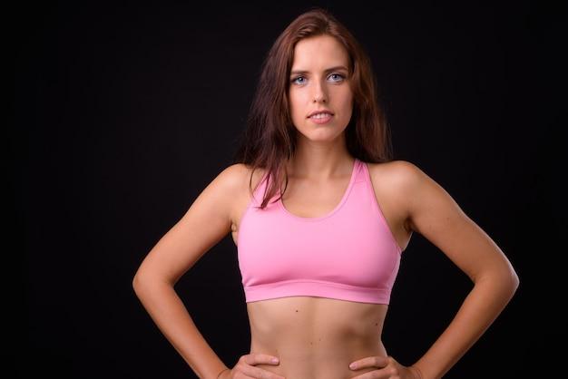 Portret van jonge mooie vrouw klaar voor sportschool tegen zwarte muur