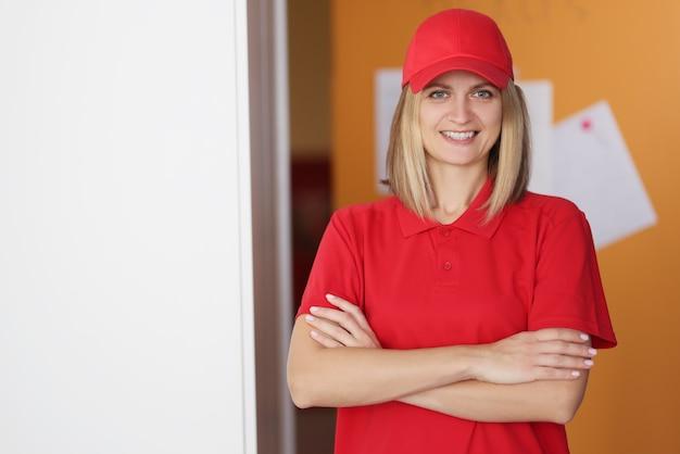 Portret van jonge mooie vrouw koerier in rood uniform