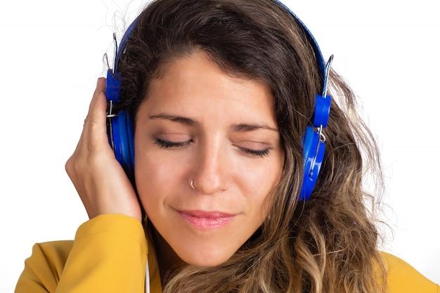 Portret van jonge mooie vrouw, luisteren naar muziek met blauwe koptelefoon op studio.