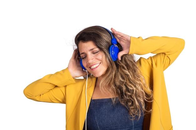 Portret van jonge mooie vrouw, luisteren naar muziek met blauwe koptelefoon
