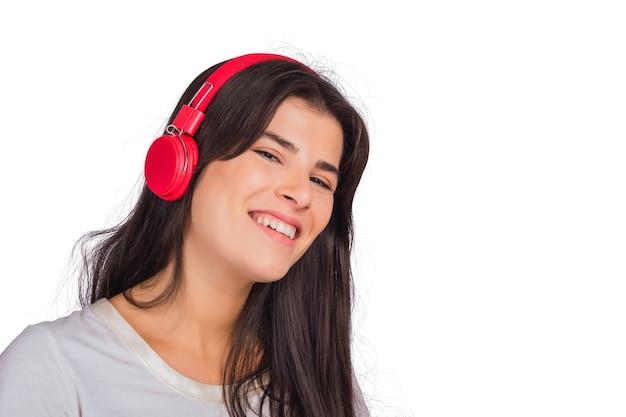 Portret van jonge mooie vrouw, luisteren naar muziek met rode koptelefoon op studio.