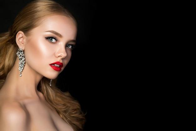 Portret van jonge mooie vrouw met avond make-up poseren op donkere achtergrond