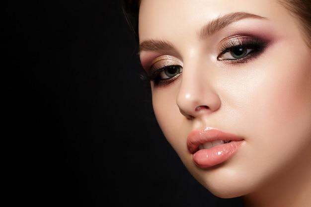 Portret van jonge mooie vrouw met avond make-up poseren op zwarte achtergrond