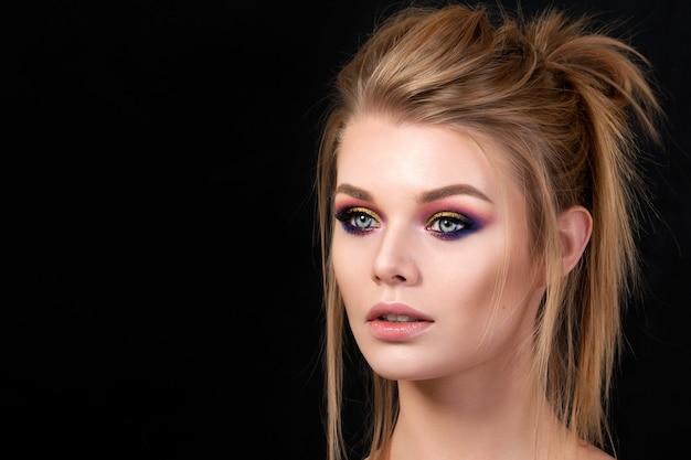 Portret van jonge mooie vrouw met avond make-up poseren. rode en gouden veelkleurige smokey eyes. luxe huidverzorging en modern mode-make-upconcept.