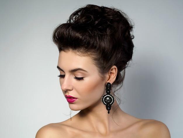 Portret van jonge mooie vrouw met avondmake-up en kapsel