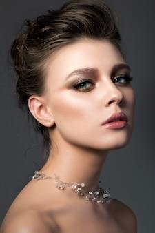 Portret van jonge mooie vrouw met bruids make-up en kapsel. moderne smokey eyes make-up