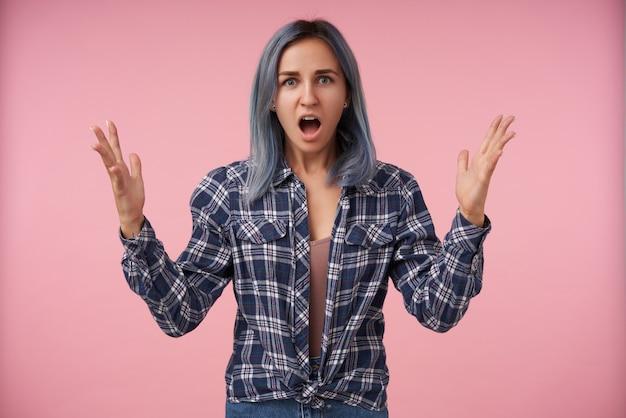 Portret van jonge mooie vrouw met casual kapsel emotioneel palmen verhogen terwijl op zoek verward met geopende mond, geïsoleerd op roze