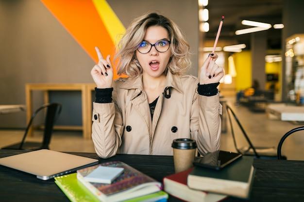 Portret van jonge mooie vrouw met een idee, zittend aan tafel in trenchcoat bezig met laptop in co-working office, bril, bezig, denken, probleem