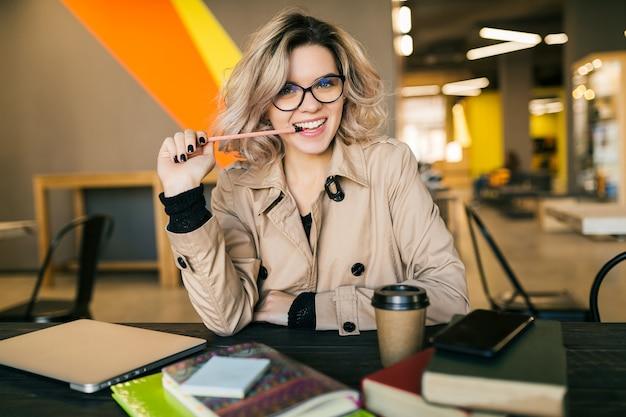 Portret van jonge mooie vrouw met een idee, zittend aan tafel in trenchcoat die op laptop werkt