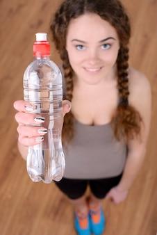 Portret van jonge mooie vrouw met fles water.