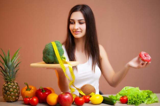 Portret van jonge mooie vrouw met groenten, fruit en meetlint
