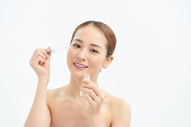 Portret van jonge mooie vrouw met huidverzorging, serumproduct op witte achtergrond