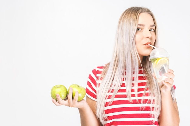 Portret van jonge mooie vrouw met in handen glas water en verse groene appel geïsoleerd over wit.