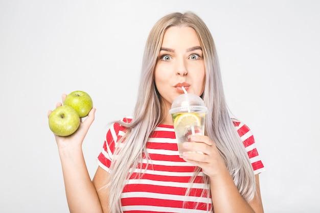 Portret van jonge mooie vrouw met in handen glas water en verse groene appel